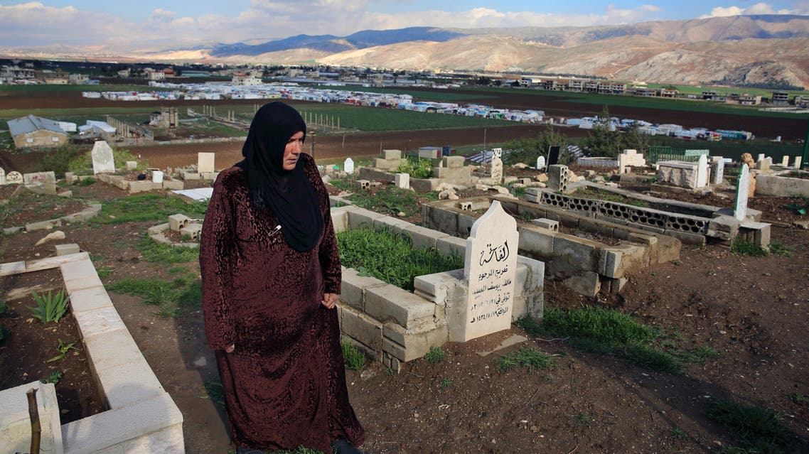 In this Tuesday, March 29, 2016 photo, Syrian refugee Saada Khalaf, 45, who fled from the city of Homs, Syria, walks in the cemetery in the eastern village of Dalhamyeh, in the Bekaa valley, Lebanon. (AP)