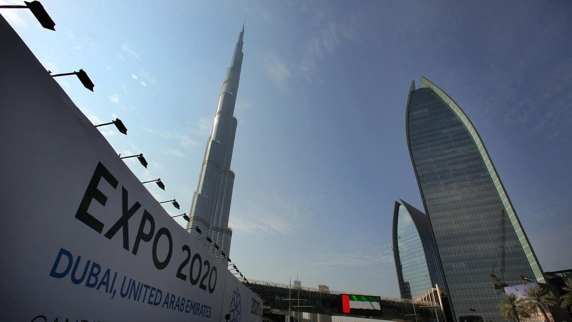 In this Wednesday Nov. 20, 2013, with the Burj Khalifa, the world's tallest building in the background, vehicles pass by a billboard advertising Dubai as a candidate city for the Expo 2020 in Dubai, United Arab Emirates. (AP)