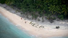 A scene from 'Castaway:' Men spell 'HELP' with palm leaves on island