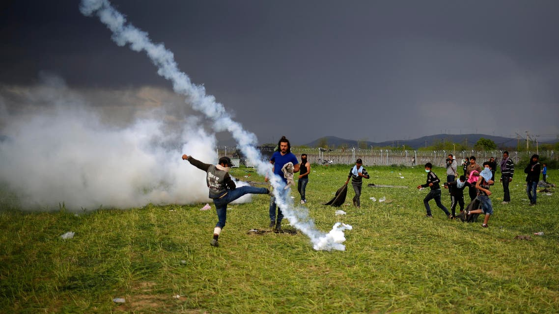 A teargas canister thrown by Macedonian police lands among protesting migrants during clashes next to a border fence at a makeshift camp for refugees and migrants at the Greek-Macedonian border near the village of Idomeni, Greece, April 10, 2016. (Reuters)