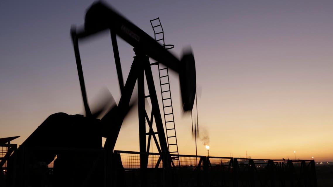 An oil pump works at sunset Monday, Jan. 18, 2016, in the desert oil fields of Sakhir, Bahrain. (AP)
