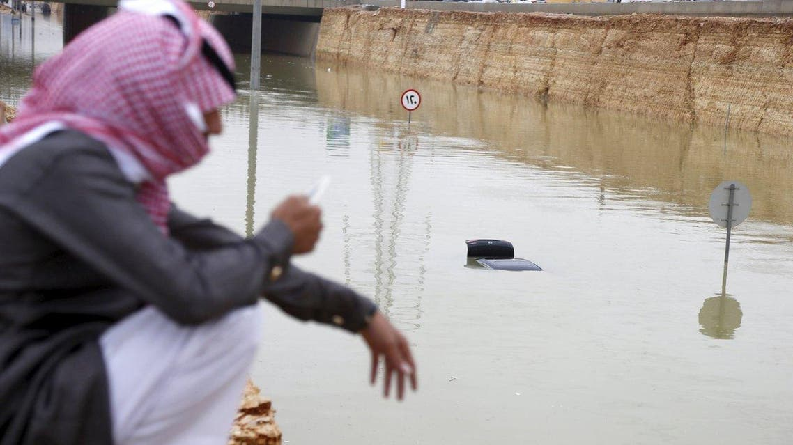 A Saudi man uses his mobile phone near a car submerged in flood waters following heavy rain, in Riyadh, Saudi Arabia November 25, 2015. (File photo: Reuters)