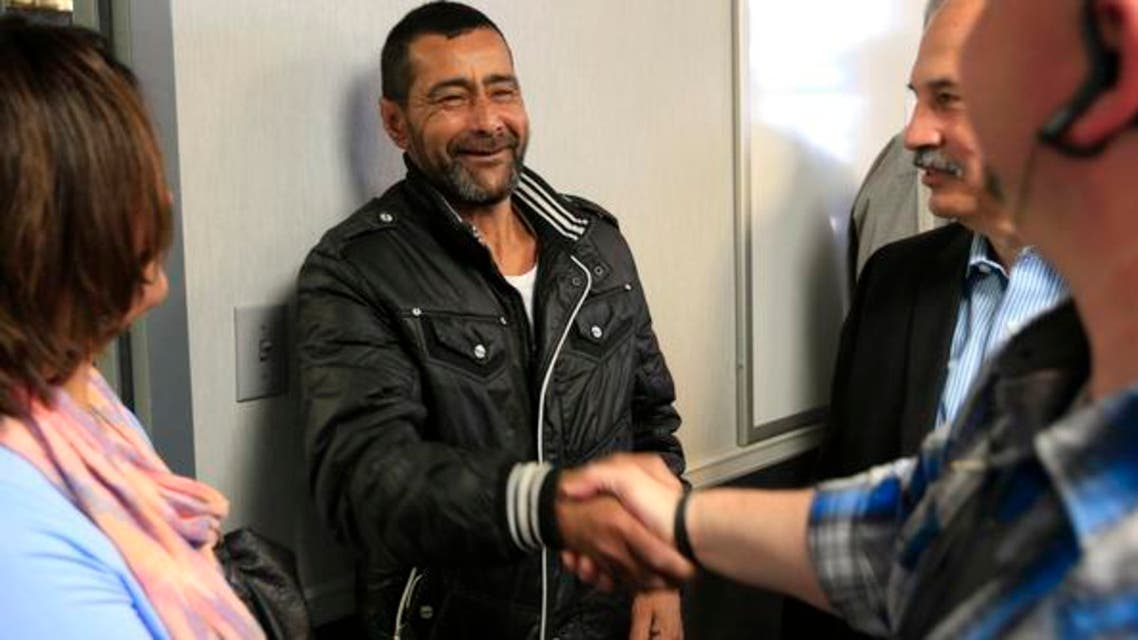 "Ahmad al-Abboud, center, shakes hands with a reporter following a news conference at Della Lamb Community Services in Kansas City, Mo., Monday, April 11, 2016. Ahmad al-Abboud and his family are the first Syrian family to be resettled in the U.S. under a speeded-up ""surge operation"" for refugees. (AP)"