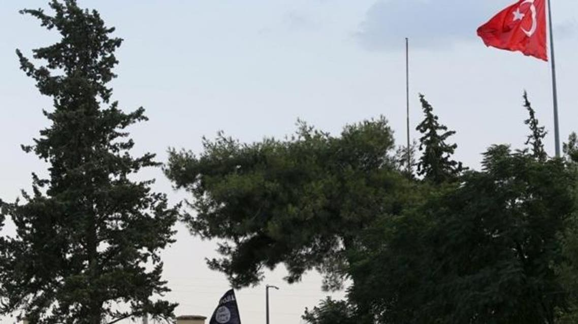 A Turkish flag flies over the Karkamis border crossing, with an ISIS flag is seen at the custom office of Syria's Jarablus border gate in the background, in Karkamis, in Gaziantep province, Turkey in this August 1, 2015 file photo. REUTERS/Murad Sezer/Files