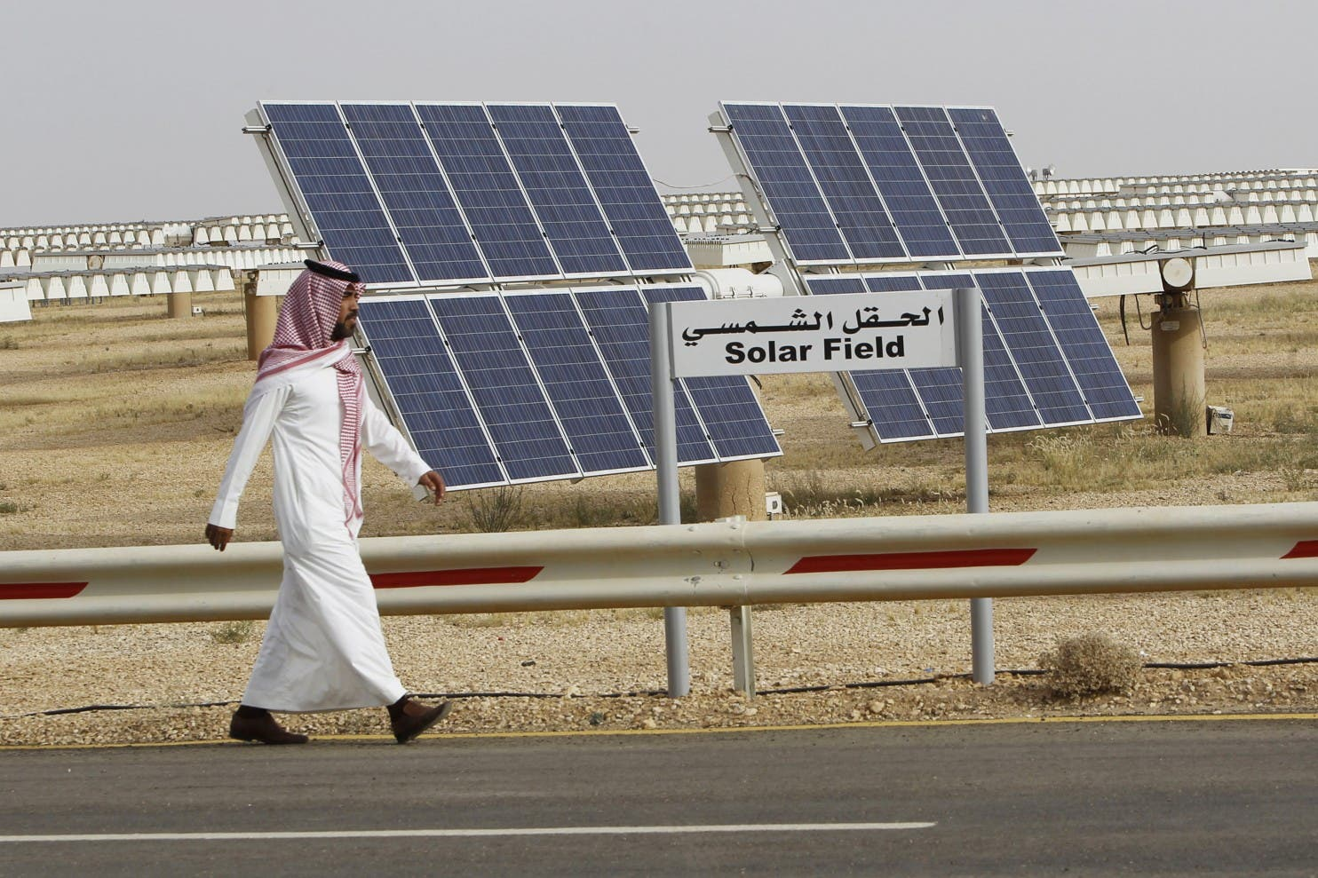 A Saudi man walks on a street past a field of solar panels at the King Abdulaziz city of Sciences and Technology, Al-Oyeynah Research Station. (File photo: Reuters)