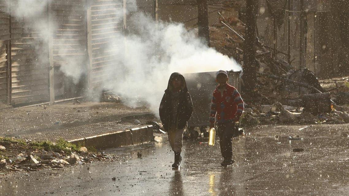 Children walk in the rain in the rebel held area of Aleppo's Seif al-Dawla district. (Reuters)