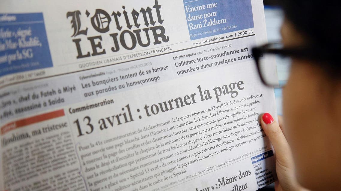 """A woman holds a Lebanese newspaper with its front page appealing for readers to """"turn the page"""" on sectarian divisions, on the 41st anniversary of the eruption of Lebanon's civil war, on April 13, 2016. On April 13, 1975, clashes erupted in Beirut between Lebanese Christians and Palestinians, marking the beginning of the 15-year war that left more than 150,000 dead. Although the conflict officially ended in 1990, Lebanon remained plagued by instability, corruption, and bitterly divided political factions.  / AFP / ANWAR AMRO"""