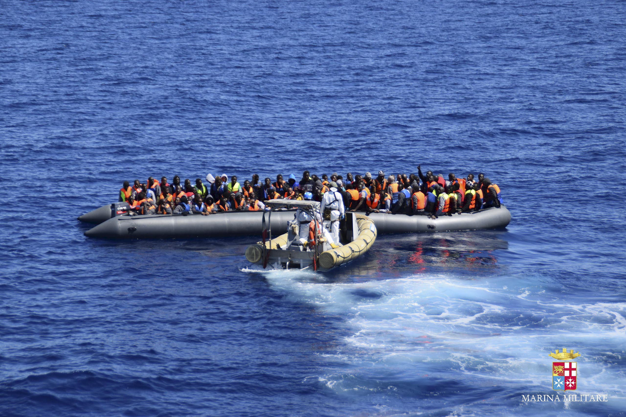 Migrants sit in their boat during a rescue operation by Italian Navy vessels off the coast of Sicily in this April 11, 2016 handout picture provided by Italy's Marina Militare. (Reuters)