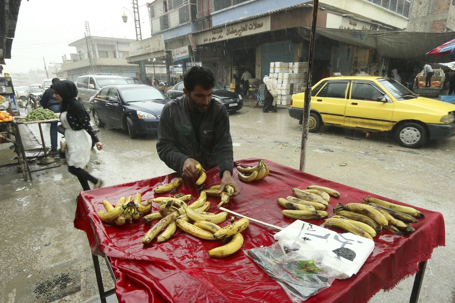 A vendor arranges bananas in a vegetable market in Qamishli. (Reuters)