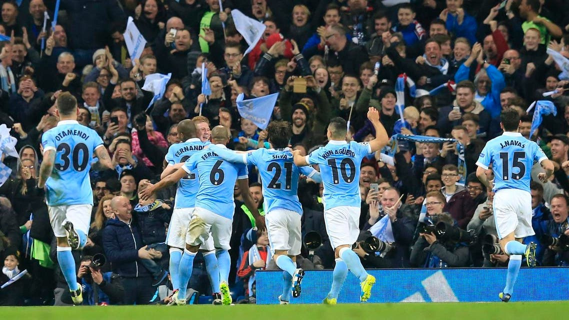 Manchester City's Kevin De Bruyne, facing turns to his teammates as he celebrates scoring the opening goal of the game during the Champions League quarterfinal second leg soccer match between Manchester City and Paris Saint Germain at the City of Manchester stadium in Manchester, England Tuesday, April 12, 2016. (AP Photo/ Jon Super)