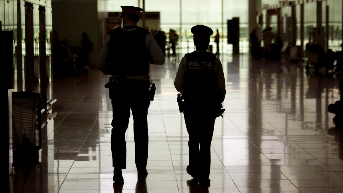 Police officers patrol inside a terminal of the airport during tighter security measures in Barcelona, Spain, Tuesday, March 22, 2016