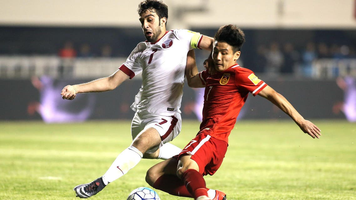 Wu Lei of China against Khaled Muftah of Qatar as Wu scores the second goal for China. (Reuters)
