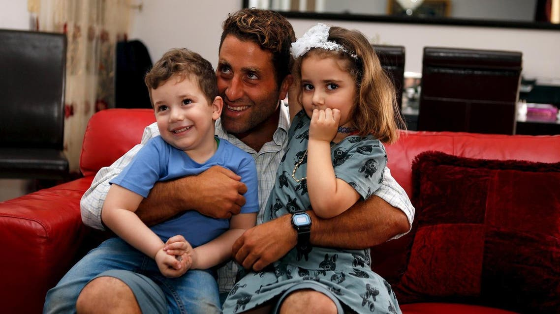 Noah and Lahela al-Amin pose for a picture with their father Ali Zeid al-Amin in their family home in Beirut, Lebanon. (Reuters)
