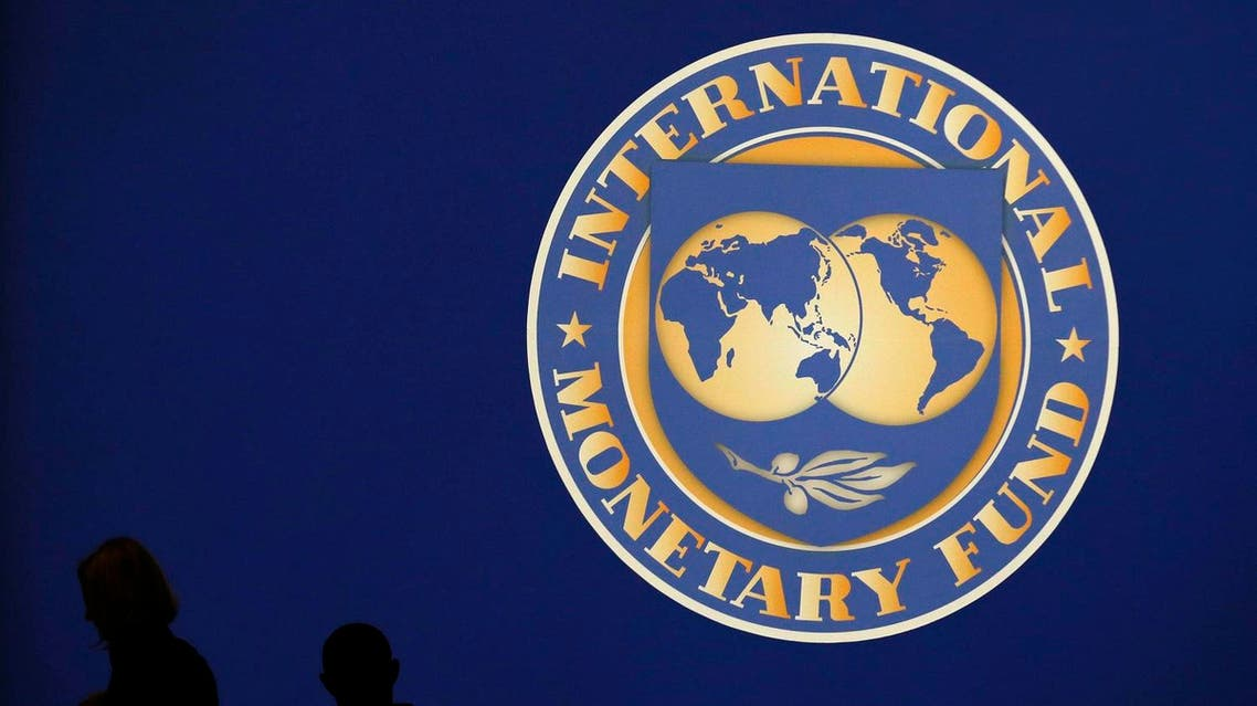 Visitors are silhouetted against the logo of the International Monetary Fund at the main venue for the IMF and World Bank annual meeting in Tokyo. (File photo: Reuters)