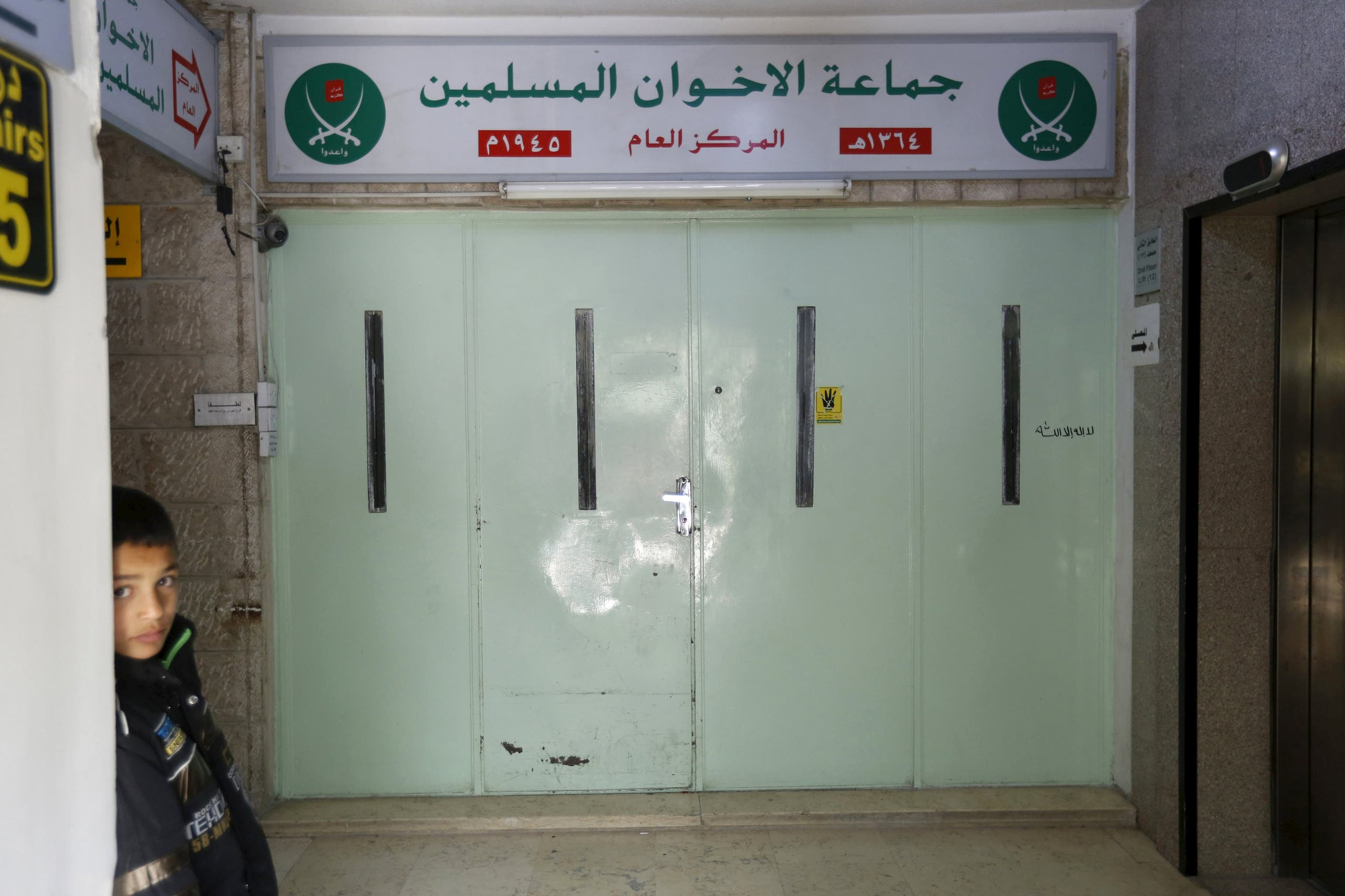 A boy who stands near the main entrance of the Muslim Brotherhood's office in Amman, after it was shut by police acting on orders of the Amman governor April 13, 2016. (Reuters)