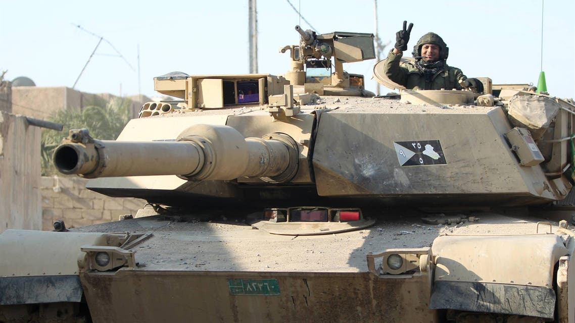 """A member of Iraq's elite counter-terrorism service flashes the """"V"""" for victory sign from inside a US-made Abrams tank. (AFP)"""