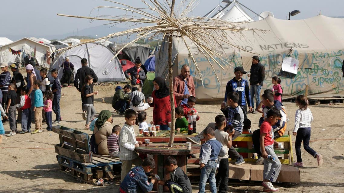 Migrant people sit and drink tea at the northern Greek border point of Idomeni, Greece, Wednesday, April 13, 2016. More than 11,000 people have been living in the makeshift camp in Idomeni for weeks after Macedonia shut its border to refugees in early March. The majority live in small tents pitched in fields and along railway tracks, while aid groups have also set up large communal tents. (AP)