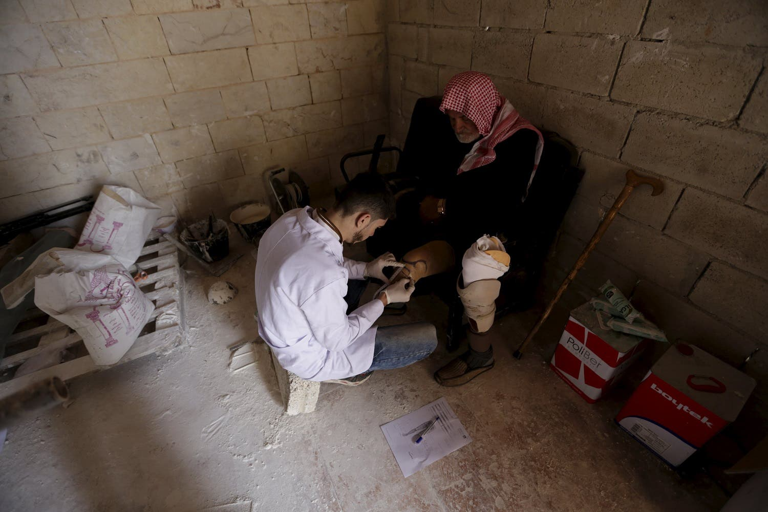 Khlouf, 25, prepares an artificial limb for a man with an amputated leg in the rebel-controlled area of Maaret al-Numan town in Idlib province, Syria March 20, 2016. REuters