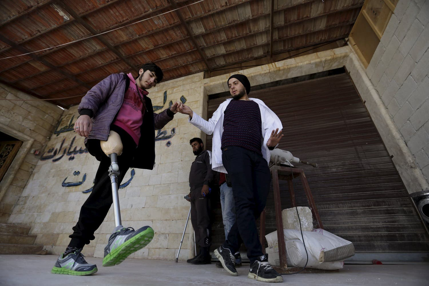 Khamis (R), 24, helps a man with an amputated leg walk using an artificial limb in the rebel-controlled area of Maaret al-Numan town in Idlib province, Syria March 20, 2016. Reuters