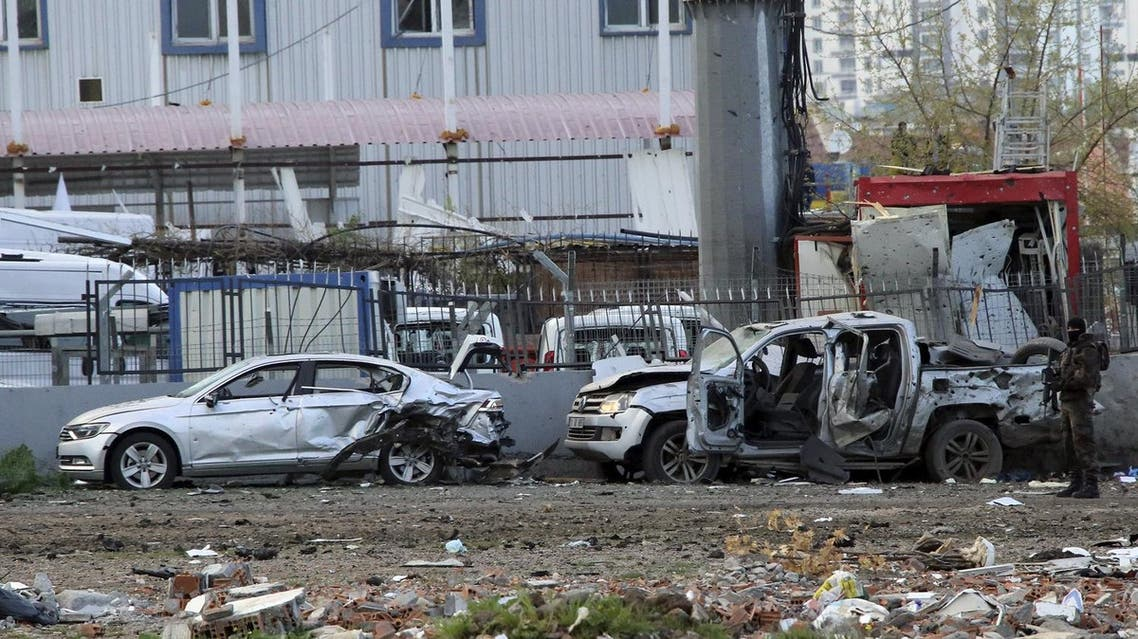 A member of the police special forces stands next to vehicles, which were damaged by a car bomb attack that targeted a minibus (not pictured) carrying members of the police special forces, occurred in the Kurdish-dominated southeastern city of Diyarbakir, Turkey March 31, 2016. REUTERS