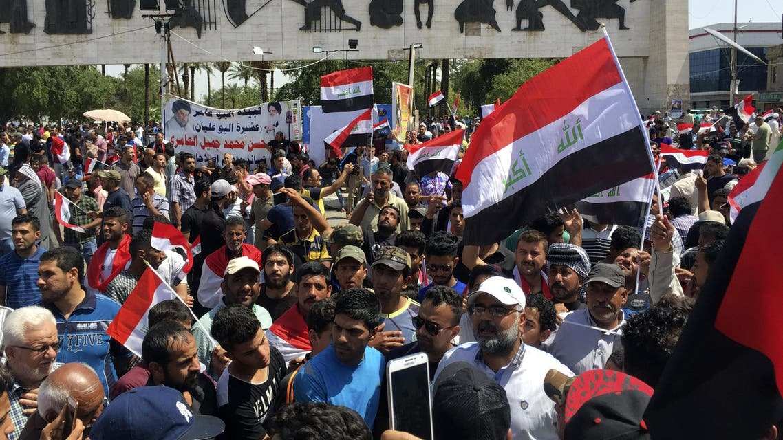 People chant anti-government slogans and wave national flags during a demonstration to protest the slow pace of reforms first promised by Prime Minister Haider al-Abadi in August 2014, in Tahrir Square, Baghdad, Iraq, Saturday, April 16, 2016.