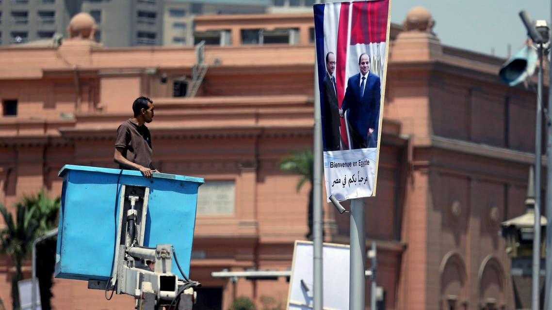A worker fixes a banner welcoming French President Francois Hollande to the country, along a bridge in central Cairo, Egypt, April 17, 2016. (Reuters)