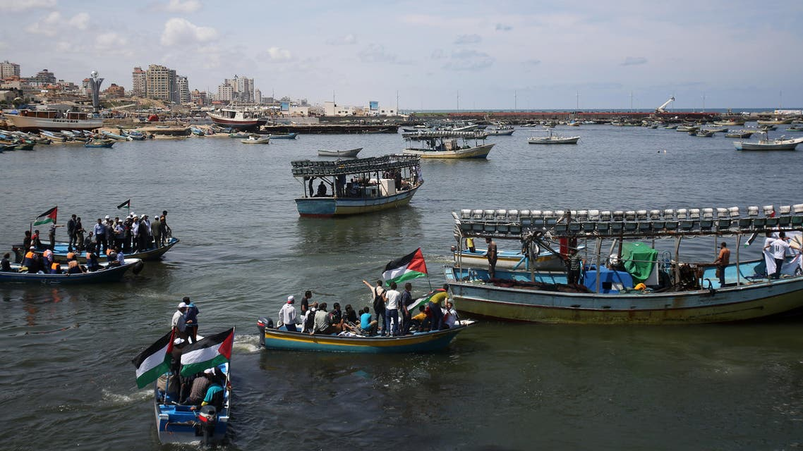 Palestinian youths wave national flags from boats during a protest organized by Palestinian activists against the Israeli naval blockade, at the fishermen's port in Gaza City, Monday, May 19, 2014. (AP)