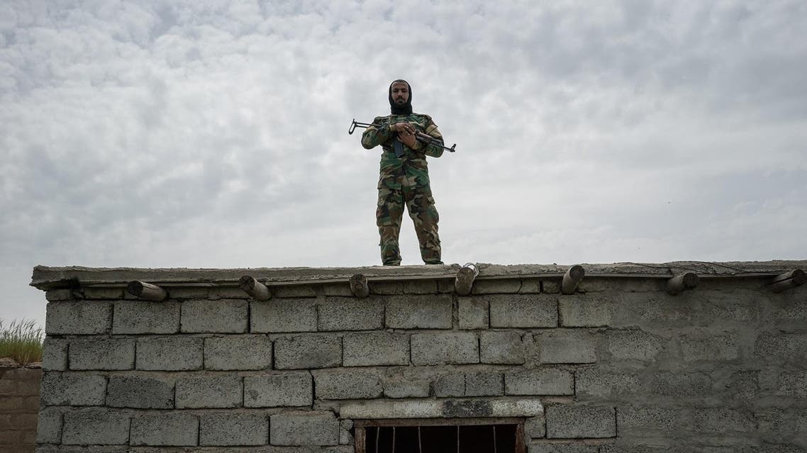 In this April 9, 2016 photo, a fighter with the Shamar tribal militia stands guard on the border with Syria, in Rabia, northwestern Iraq. (AP)