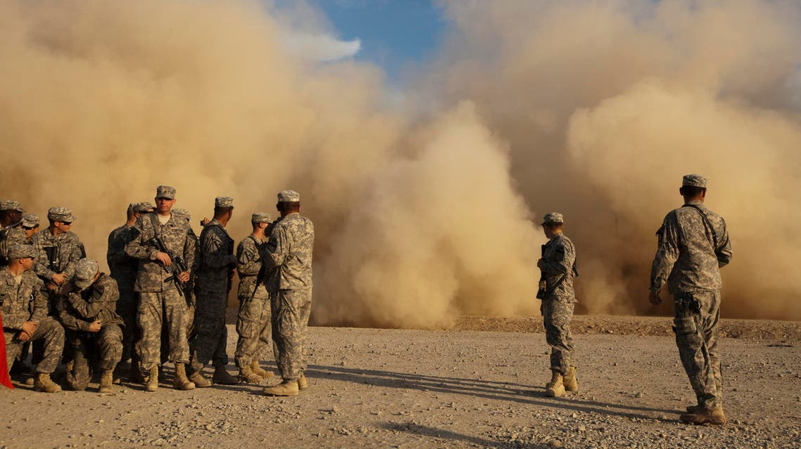 Soldiers from the 3rd Brigade Combat Team, 1st Cavalry Division watch a Blackhawk helicopter raise a sand cloud during landing as they wait at a staging area in Camp Adder to be part of the last U.S. military convoy to leave the country near Nasiriyah, Iraq on Saturday, Dec. 17, 2011. (AP)