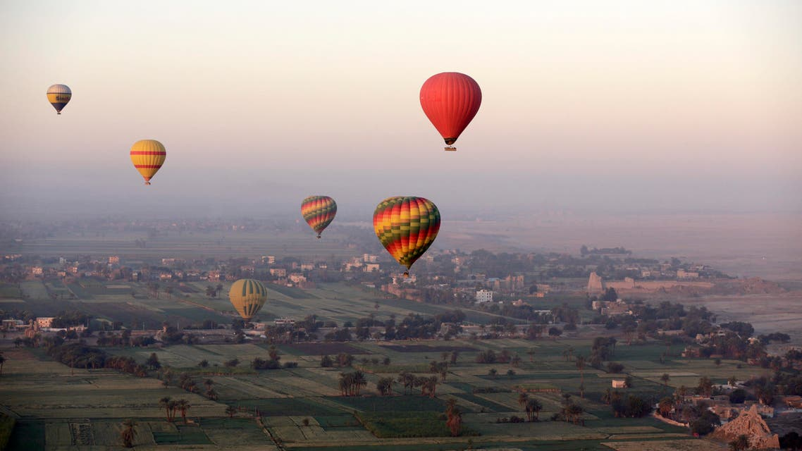 In this picture taken from a balloon Friday, April 1, 2016, hot air balloons fly over the west bank of the Nile River in Luxor, Egypt. AP
