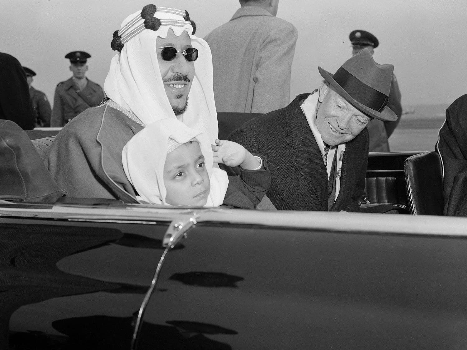 Six-year-old Prince Mashhur ibn Saud waves as he sits on the lap of his father, King Saud of Saudi Arabia, and beside President Eisenhower as they left National Airport, January 30, 1957 (File Photo: AP)