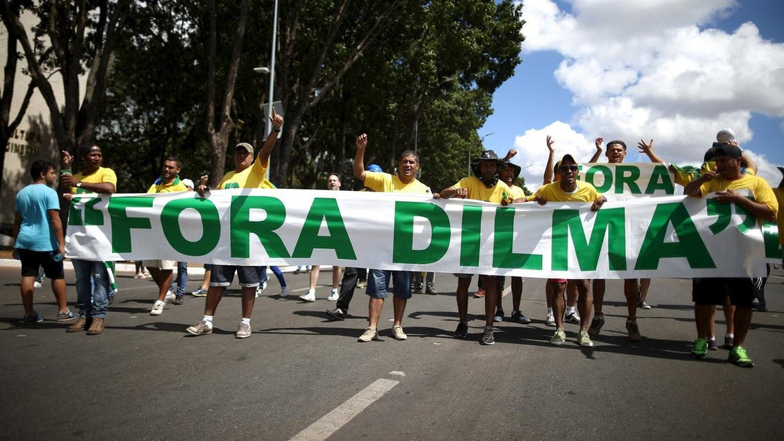 """Protesters hold a banner reading """"Dilma out"""", ahead of Brazilian President Dilma Rousseff's impeachment vote, in Brasilia, Brazil April 17, 2016. (Reuters)"""