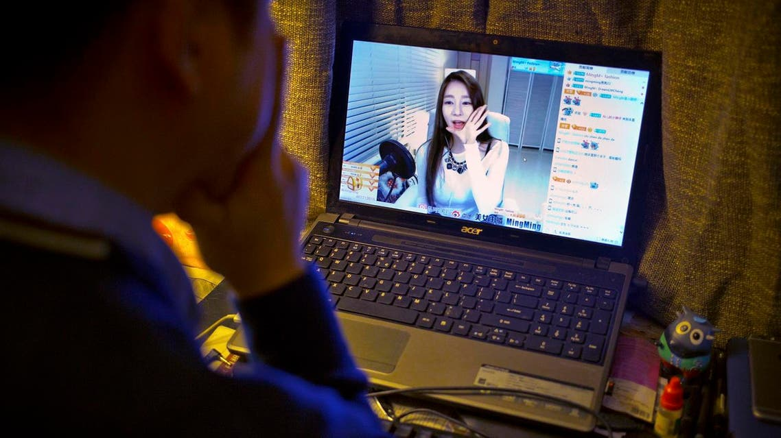 In this Feb. 28, 2016 photo, office worker Zhai, 28, who asked that only his last name be used, pets his cat while watching a live web stream from a Korean web performer on his computer at his apartment in Beijing. (AP)