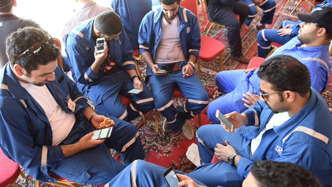 Kuwait Oil and Petrochemical Industries Union workers sit with their cellphones on the first day of an official strike over public sector pay reforms, in Ahmadi, Kuwait April 17, 2016. Reuters