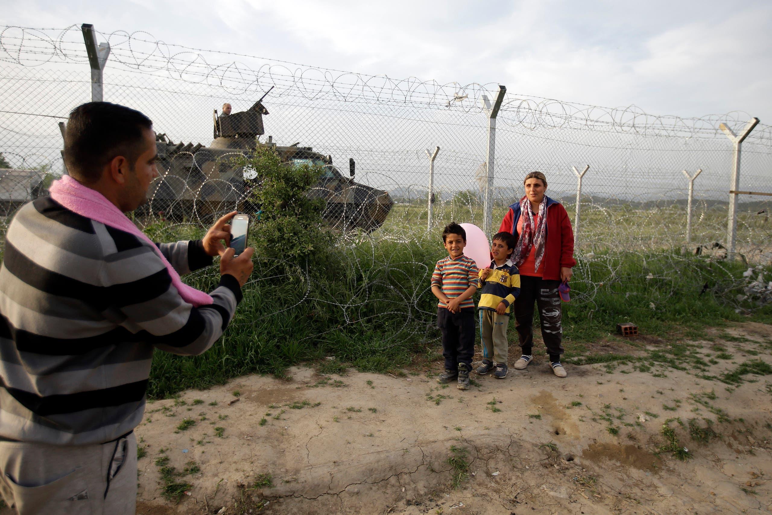 Migrants wait to cross into Macedonia