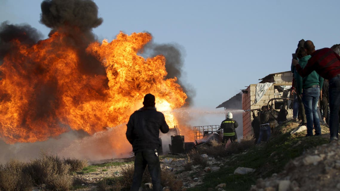 Civil Defence members put out a fire that spread in an oil refinery in the town of Marat Numan in Idlib province, Syria March 10, 2016. (Reuters)