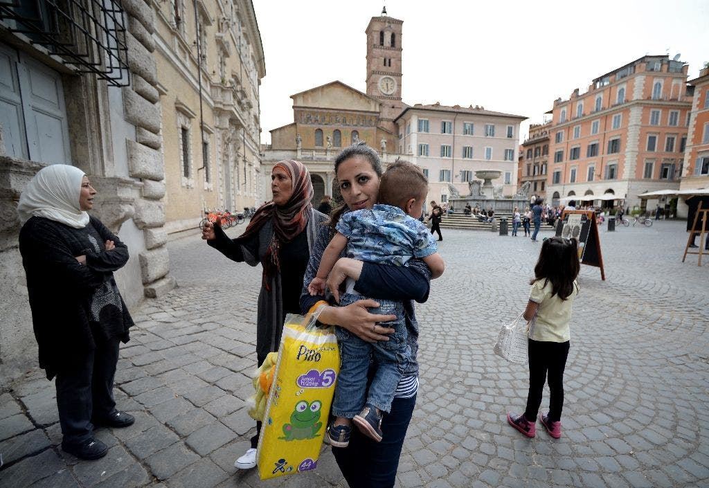 Nour, 30, a Syrian refugee and one of the 12 Syrian asylum seekers Pope Francis brought back with him from Greek island of Lesbos, holds her son Riad, 2, as she arrives at the St. Egidio Roman Catholic Charity in Rome on April 18, 2016 (AFP)