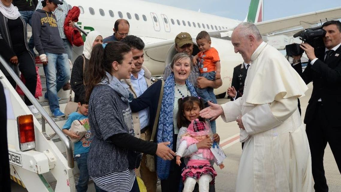 Pope Francis welcomes a group of Syrian refugees after landing at Ciampino airport in Rome following a visit at the Moria refugee camp on the Greek island of Lesbos on April 16, 2016 (AFP)