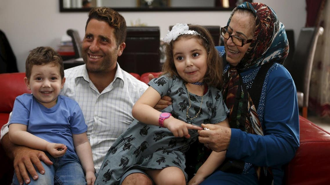 Noah (L) and Lahela al-Amin (2nd R) pose for a picture with their father Ali Zeid al-Amin (2nd L) and grandmother in their family home in Beirut, Lebanon April 8, 2016. Picture taken April 8, 2016. (Reuters)