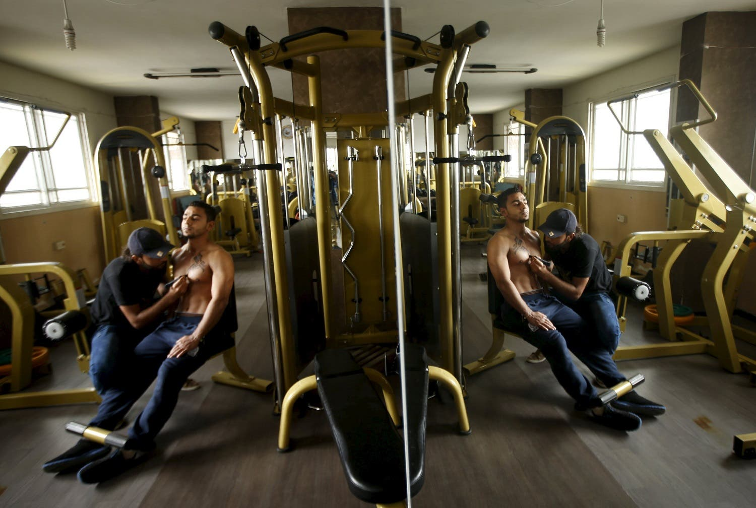 Palestinian artist Bilal Khaled is reflected in a mirror as he paints Arabic letters on a bodybuilder in a gym in Gaza City April 12, 2016. REUTERS