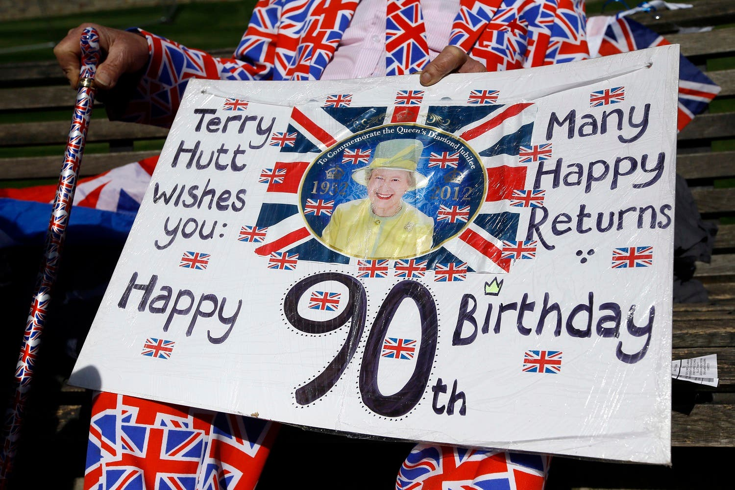 Terry Hutt, a royal fan shows a card he has made, in Windsor, England, Wednesday, April 20, 2016. Royal fans are gathering in Windsor ahead of Thursday's celebrations for the 90th birthday of Britain's Queen Elizabeth II. (AP)