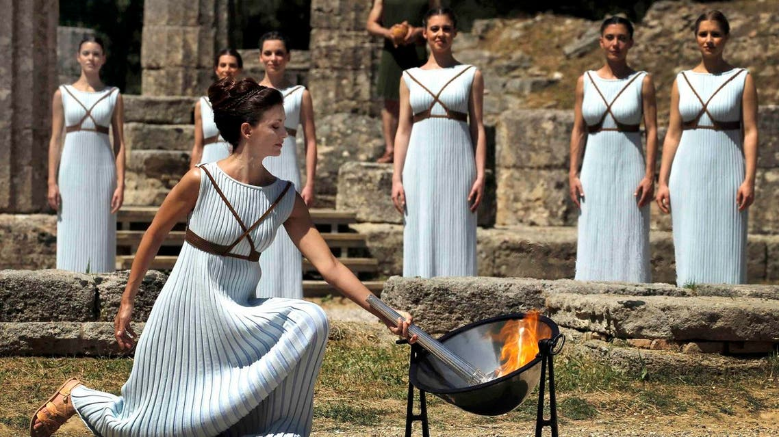 Greek actress Katerina Lehou , playing the role of High Priestess, lights a torch from the sun's rays reflected in a parabolic mirror during the dress rehearsal for the Olympic flame lighting ceremony for the Rio 2016 Olympic Games at the site of ancient Olympia in Greece, April 20, 2016. REUTERS