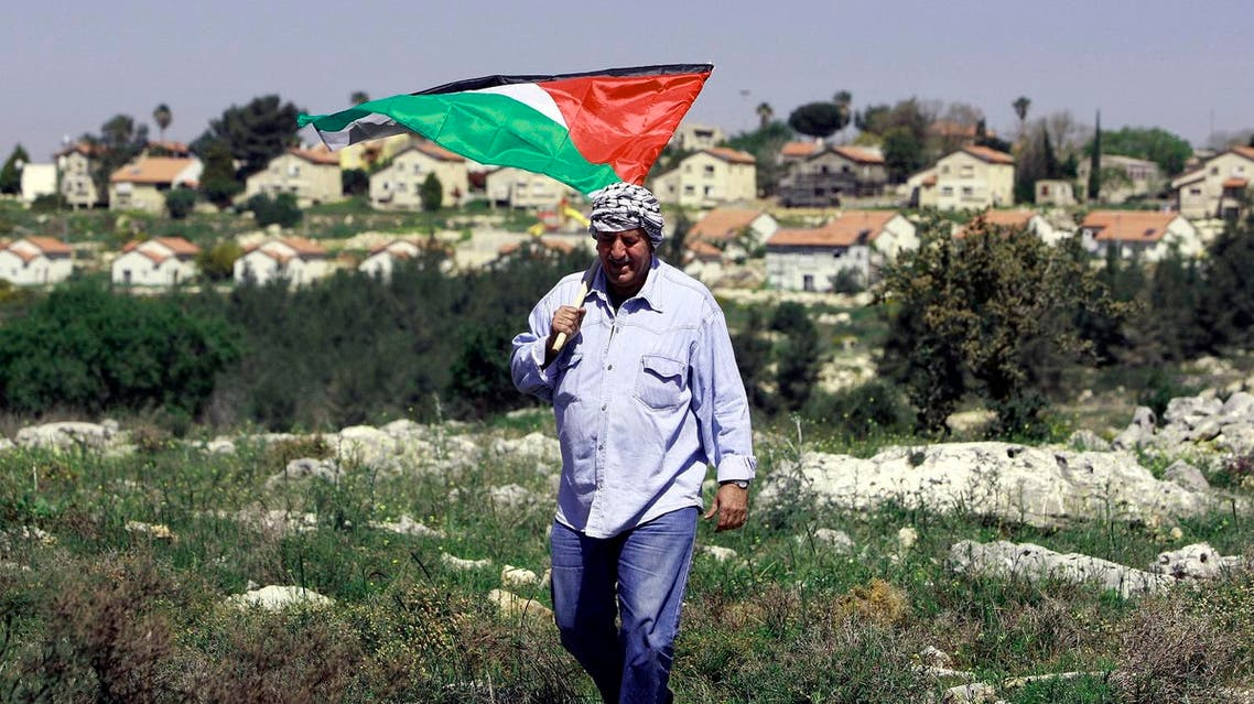 A Palestinian man holds the national flag during a rally marking the Land Day close to the Jewish settlement of Mavo Dothan, south Jenin city, Monday, March 31, 2014. (AP)