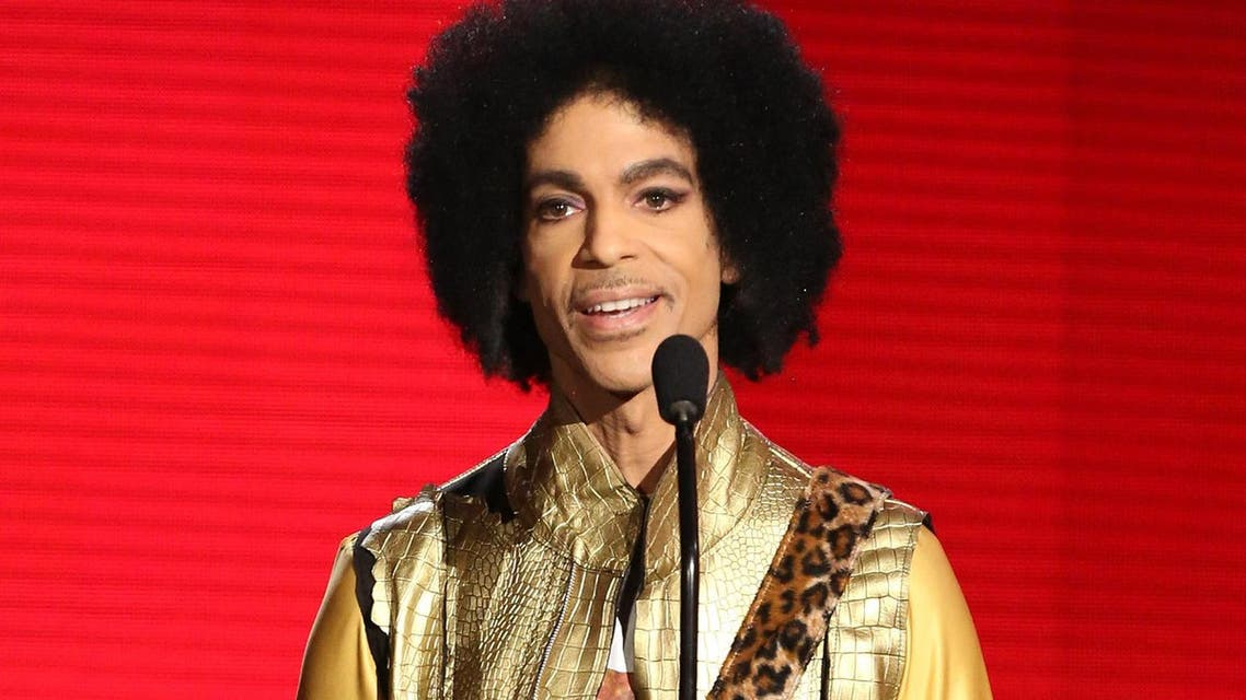 """In this Nov. 22, 2015 file photo, Prince presents the award for favorite album - soul/R&B at the American Music Awards in Los Angeles. Prince, widely acclaimed as one of the most inventive and influential musicians of his era with hits including """"Little Red Corvette,"""" ''Let's Go Crazy"""" and """"When Doves Cry,"""" was found dead at his home on Thursday, April 21, 2016, in suburban Minneapolis, according to his publicist. He was 57. (Photo by Matt Sayles/Invision/AP, File)"""