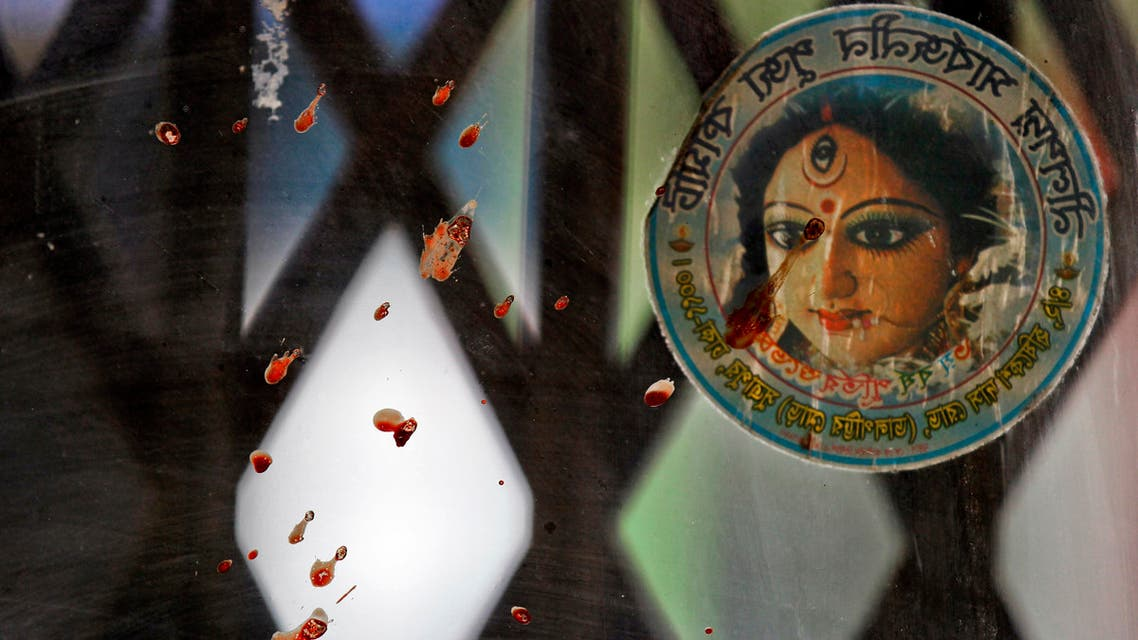 Blood stained glass and a photograph of the Hindu goddess Durga is seen near the spot where three motorcycle-riding assailants hacked student activist Nazimuddin Samad to death while walking with a friend, in Dhaka, Bangladesh, Thursday, April 7, 2016.