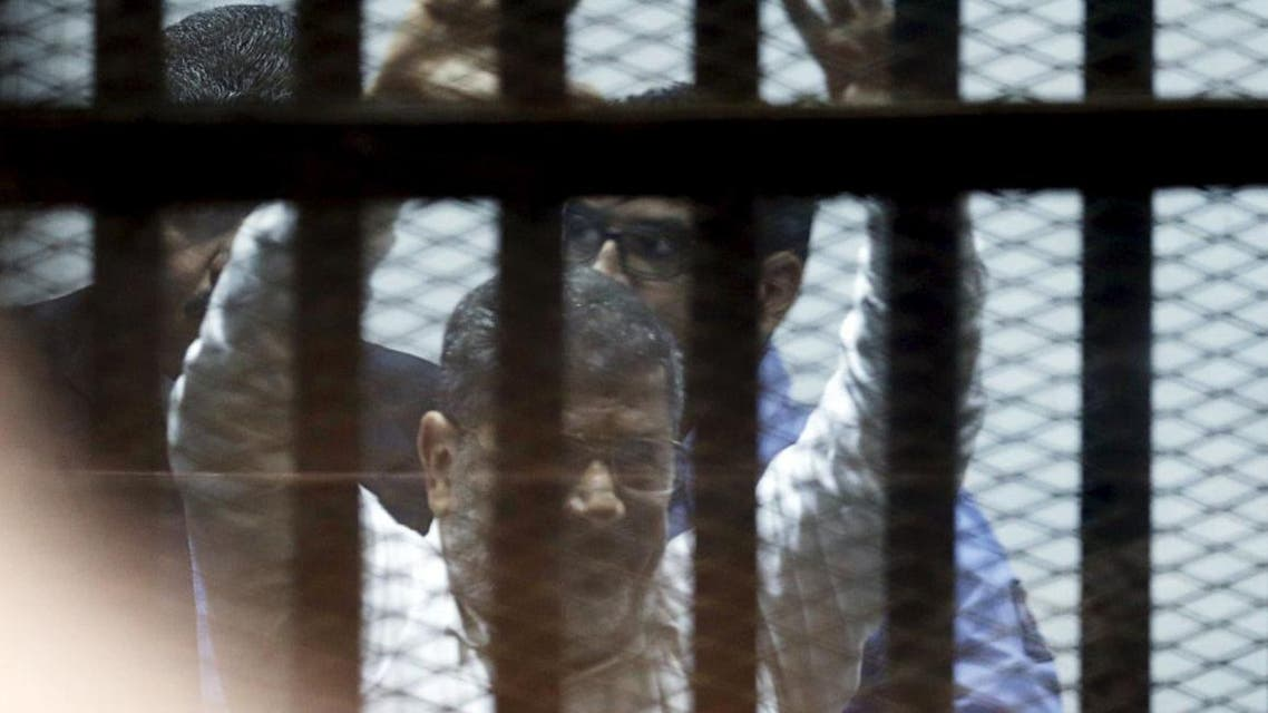 Ousted Egyptian President Mohamed Mursi gestures after his trial behind bars at a court in the outskirts of Cairo, April 21, 2015. An Egyptian court sentenced ousted President Mohamed Mursi to 20 years in prison without parole on Tuesday for the killing of protesters in December 2012, in a decision broadcast on state television. REUTERS