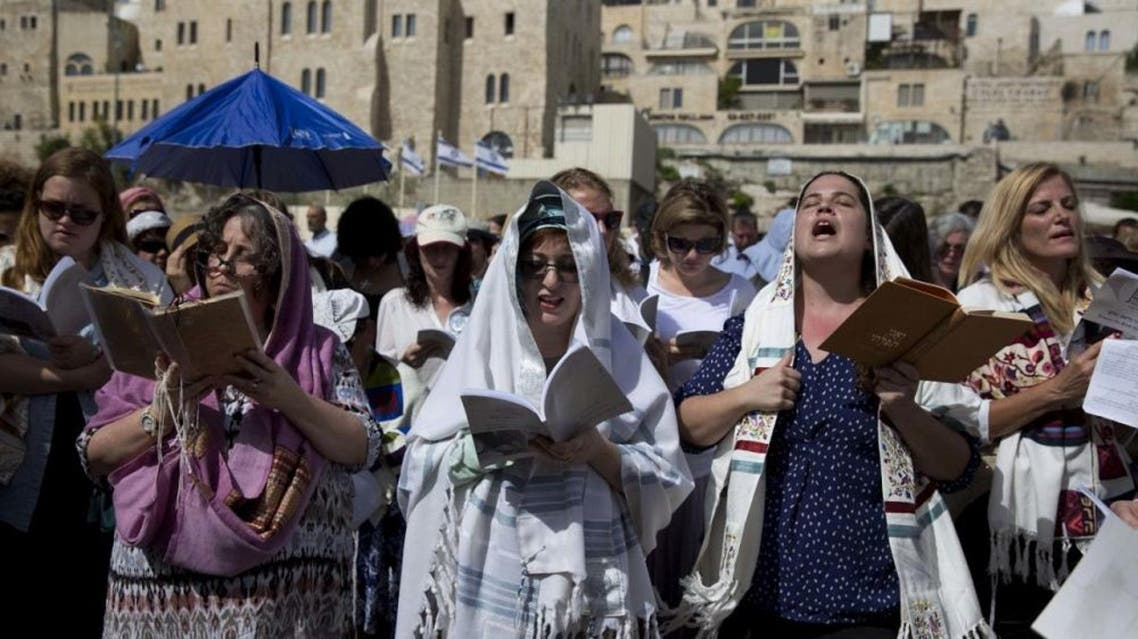 Jewish women wear prayer shawls as they pray during the Jewish holiday of Passover in front of the Western Wall, the holiest site where Jews can pray, in Jerusalem's Old City, Sunday, April 24, 2016 (AP)