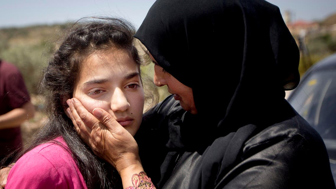 Sabha al-Wawi, right, Palestinian mother of 12-year-old Dima al-Wawi, imprisoned by Israel for allegedly attempting to carry out a stabbing attack, comforts her daughter, after her release from an Israeli prison, at Jabara checkpoint near the West Bank town of Tulkarem, Sunday, April 24, 2016. (AP)