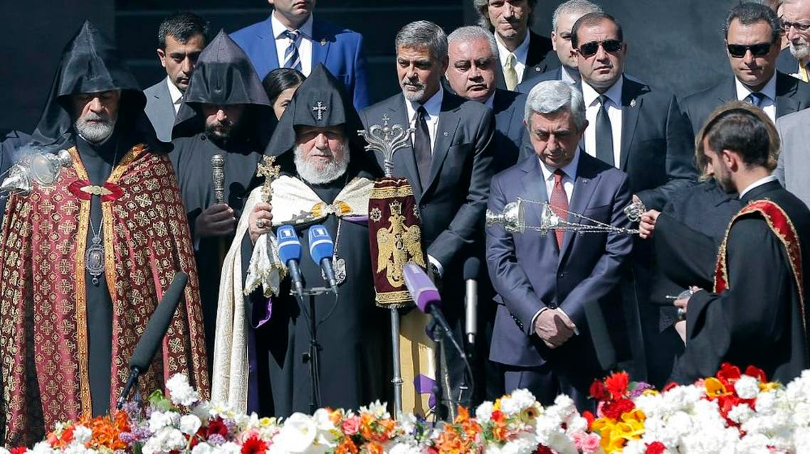 Armenian clergymen, US actor George Clooney, center, Armenian President Serzh Sargsyan, second right front, and guests attend a ceremony at a memorial to Armenians killed by the Ottoman Turks, in Yerevan, Armenia, on Sunday, April 24, 2016 (AP)