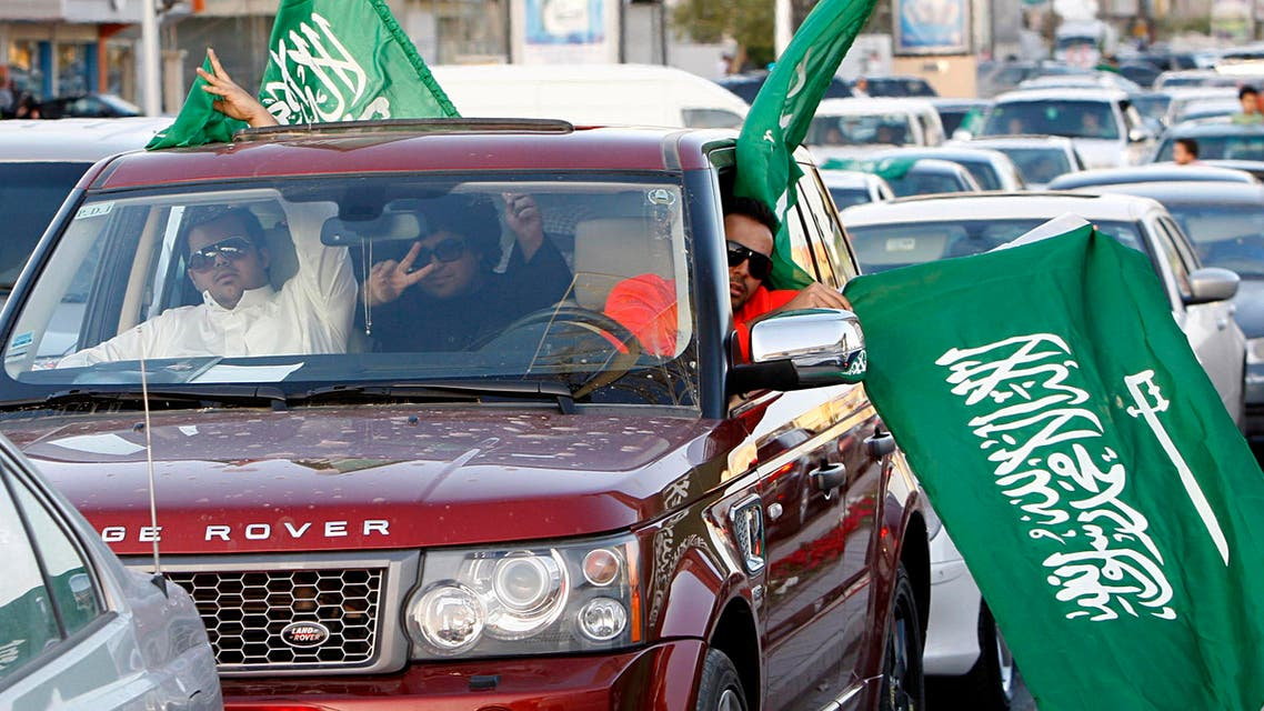 Saudi men gesture as they carry national flags during street celebrations in Riyadh, Saudi Arabia. (File photo AP)